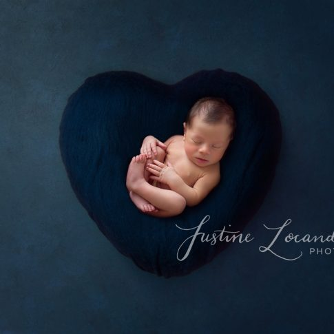 Photograph of newborn baby boy in blue heart taken by Ballarat newborn photographer Justine Locandro Photography