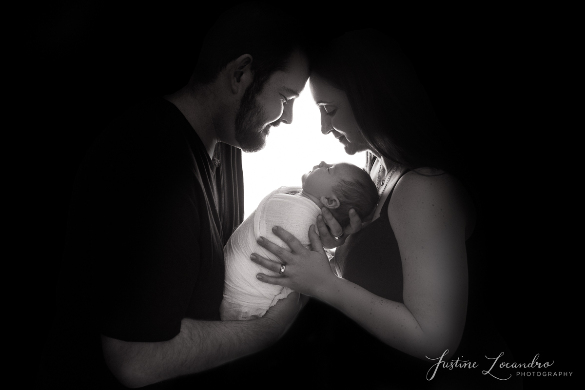 Silhouette image of mother and father and newborn daughter. Taken by Ballarat newborn photographer Justine Locandro Photography
