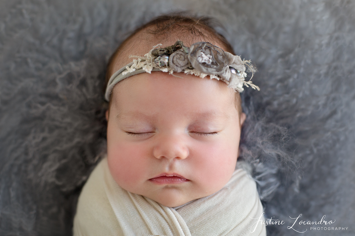 Baby girl in grey floral headband. Taken by Ballarat newborn photographer Justine Locandro Photography